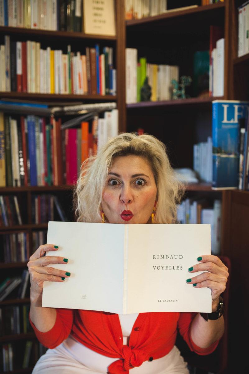 """Deborah Kunz de chez DK Rédaction, pose devant sa bibliothèque en bois de chêne. Facétieuse, elle tient un livre ouvert en simulant la surprise. On peut y lire le titre de l'ouvrage""""Voyelles de Rimbaud"""", imprimé par l'atelier typographique """"Le Cadratin"""" de Sottens. Ce livre précieux l'est autant par son contenu que par sa forme: imprimé sur une machine Heidelberg du XXe siècle."""